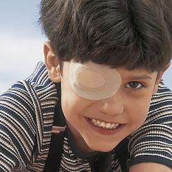 Boy with eye occlusor by Leukoplast