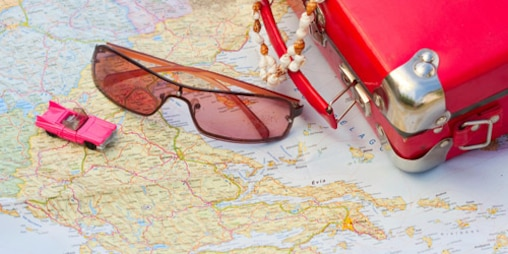 A red toy suitcase, sunglasses and a toy car are lying on a road map.