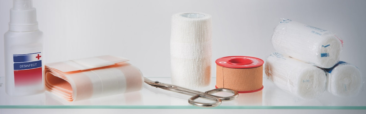 Composition of 4 rolls of bandages, a roll of adhesive wound dressing, disinfectant spray, Leukoplast fixation tape and plaster scissors on a glass table.