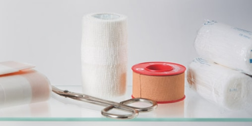 Composition of 3 gauze rolls, Leukoplast fixation tape, adhesive wound dressing and plaster scissors on a glass table.