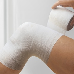Elastomull haft by Leukoplast, application of bandage on knee