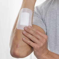 Inspection of Leukomed absorbent dressing by Leukoplast on arm